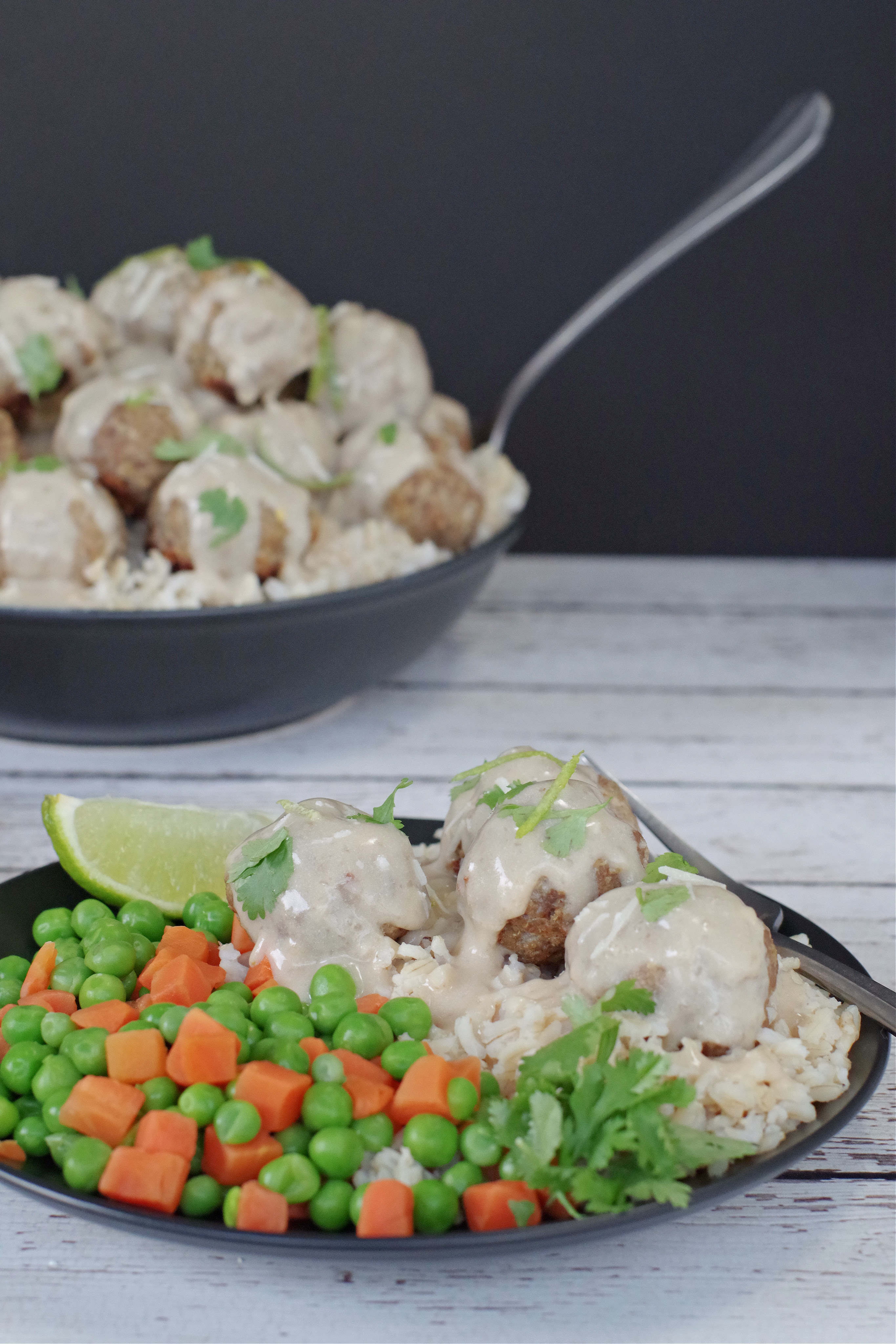 Healthy turkey meatballs with sauce on black plate, with veggies and rice and black bowl with turkey meatballs with white sauce in background