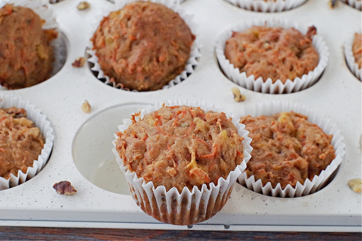 carrot muffins on a white speckled muffin tin with one sitting on top