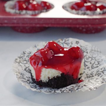 a mini cherry cheesecake on a damask print muffin wrapper, with a red speckled muffin tin ofmini cherry cheesecakes in the background