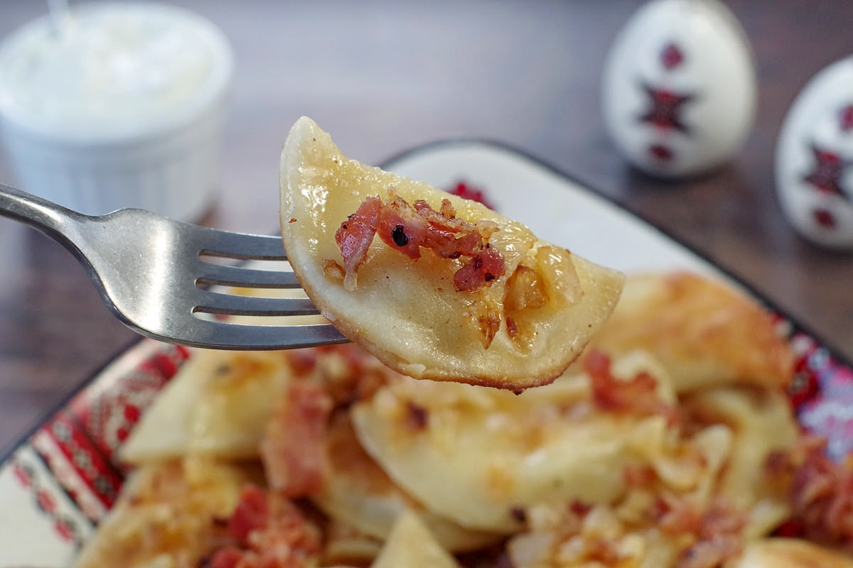 potato and cheese pierogi being held up on a fork over a dish of perogies with bacon and onion with sour cream and ukrainian print salt and pepper shakers in the background