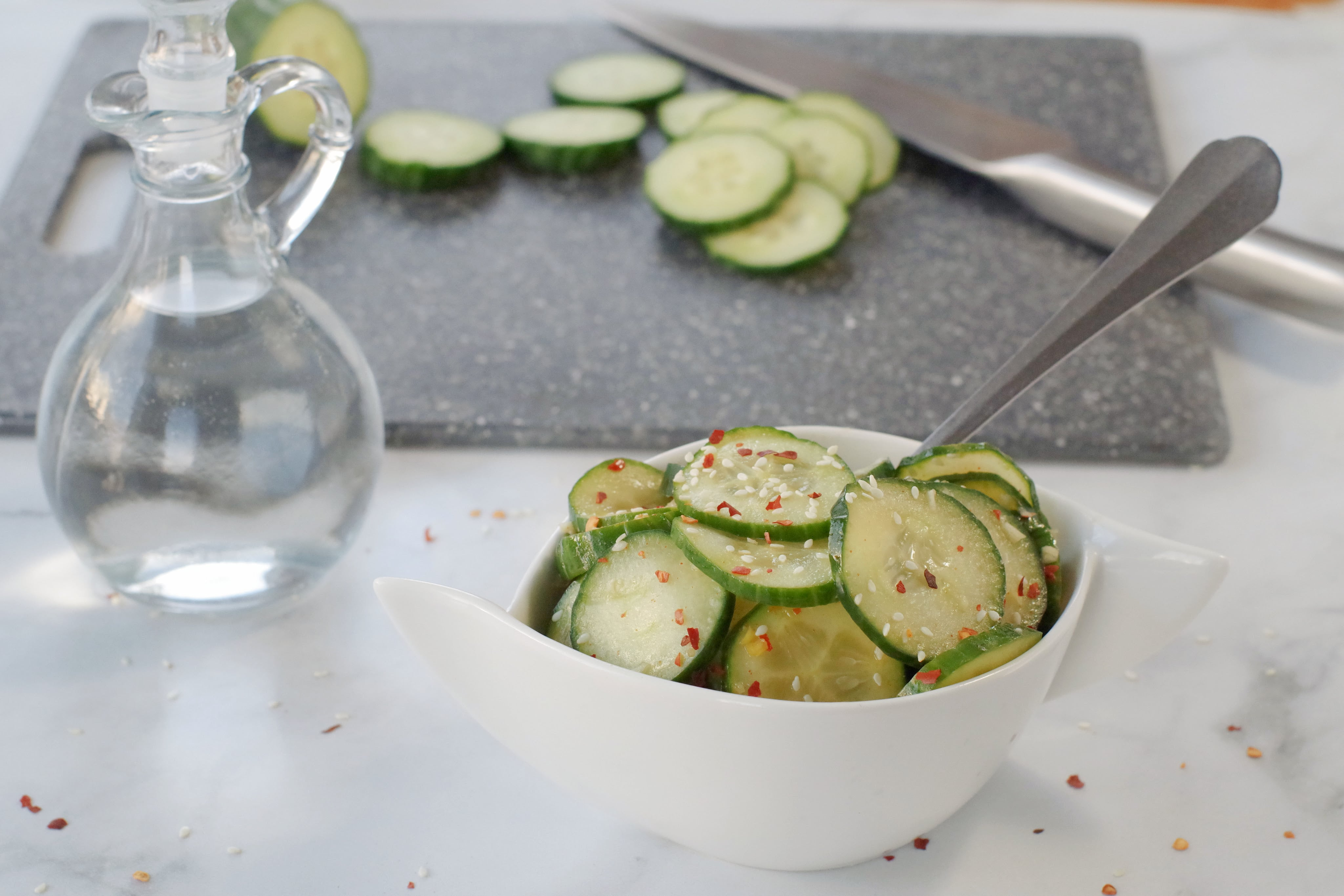 quick Kimchi on grey marble counter surface with glass vinegar container in background as well as a grey cutting board with sliced cucumbers and a knife