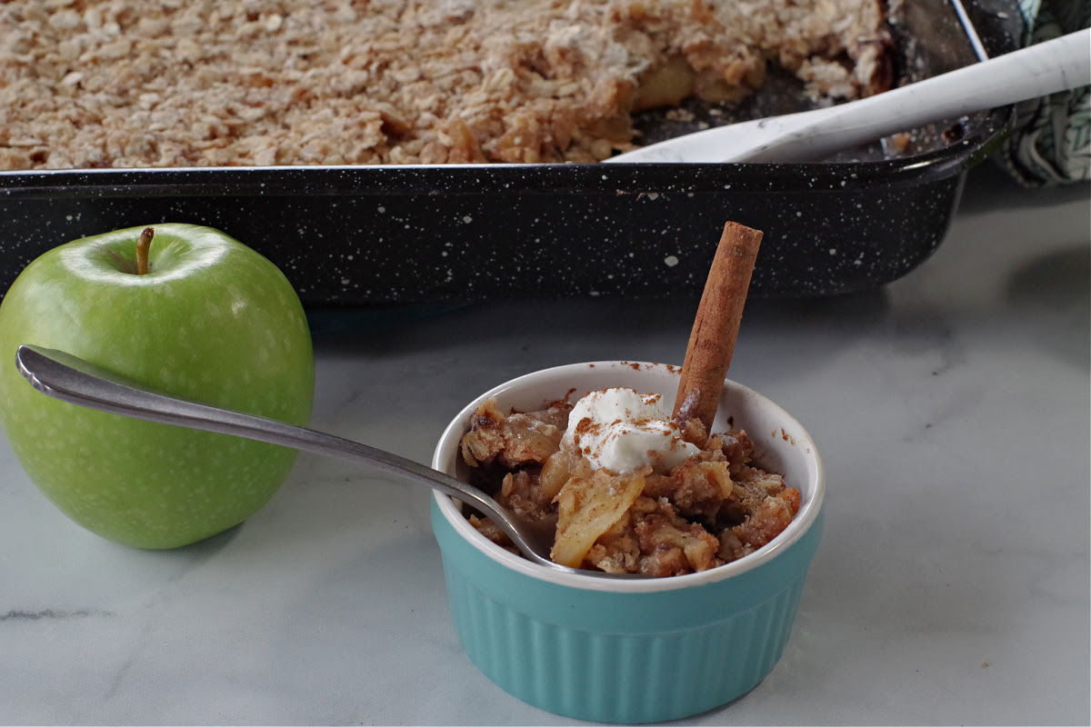 weight watchers apple crisp in a small blue bowl with a green apple and a large container in background