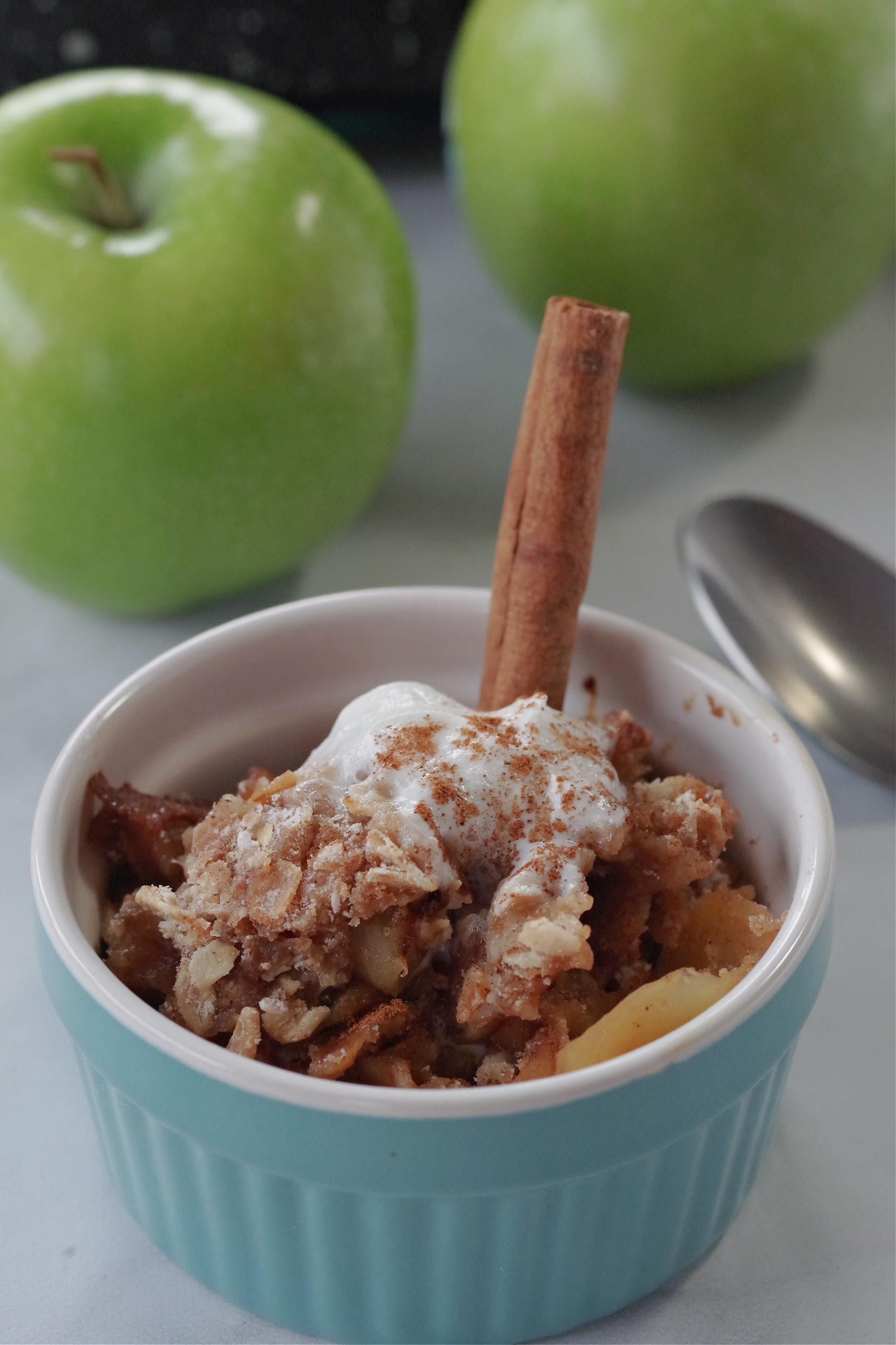 weight watchers apple crisp in a small blue bowl with a cinnamon stick in it and 2 green apples and a spoon in the background