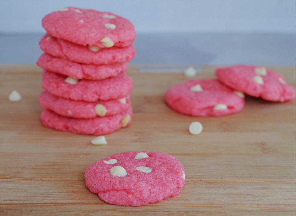 strawberry milkshake cookies on a wood cutting board, with a stack of cookies background and white chocolate chips scattered