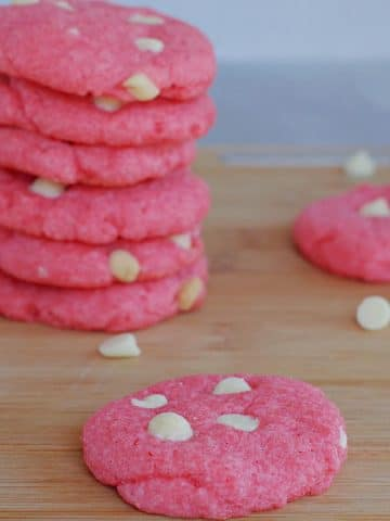 Strawberry milkshake cookie on a cutting board with pile of cookies behind
