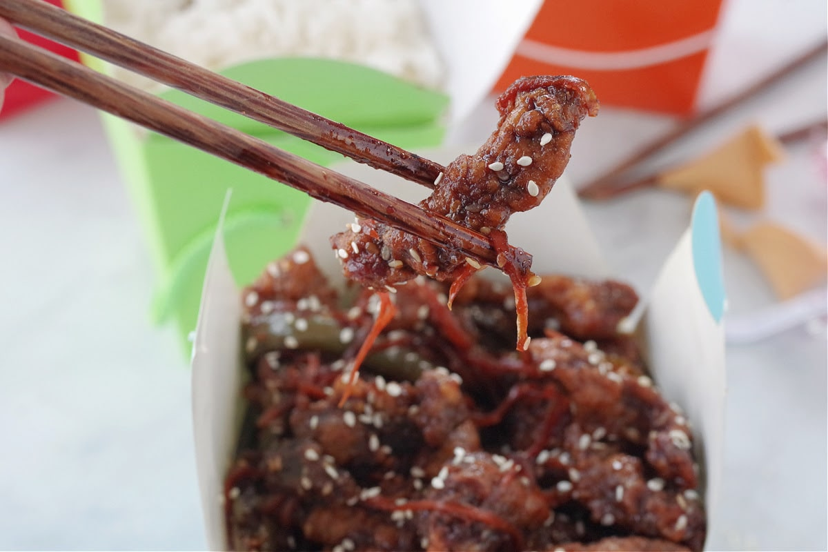 a piece of ginger beef being held up with chopsticks over a blue take-out container