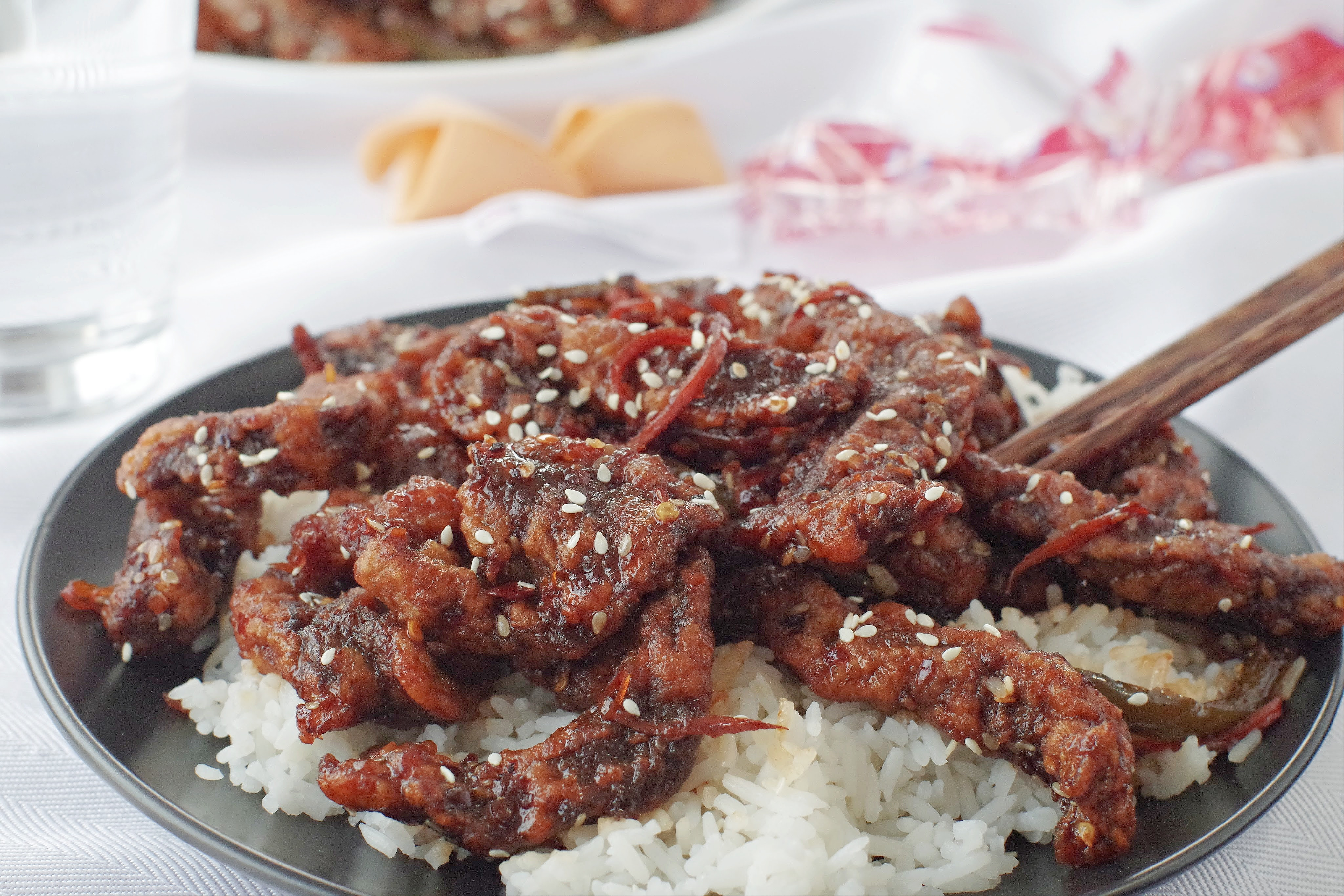 ginger beef over rice on a black plate on white table cloth, with fortune cookies