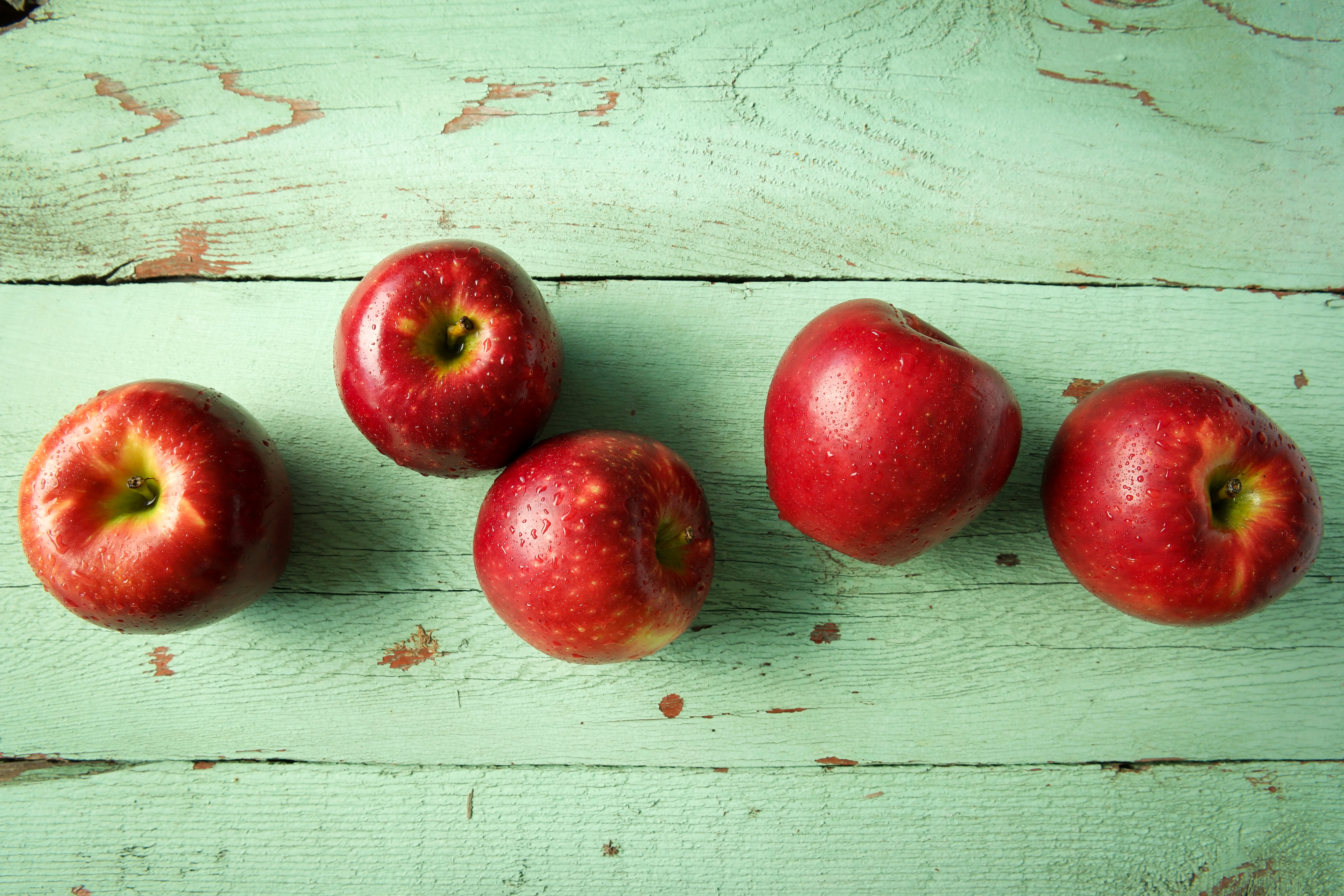 5 Cosmic Crisp apples on a green wooden background