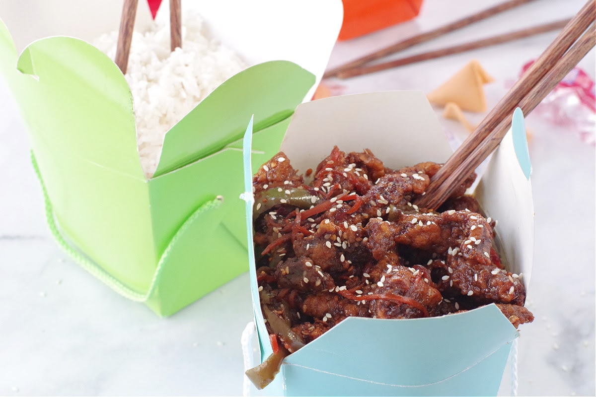 ginger beef in blue take-out container with chopsticks and green take-out container with rice in the background