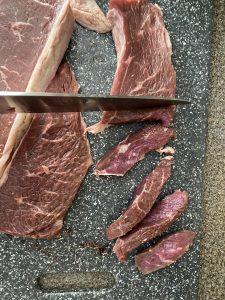 steak being cut into strips on a grey cutting board