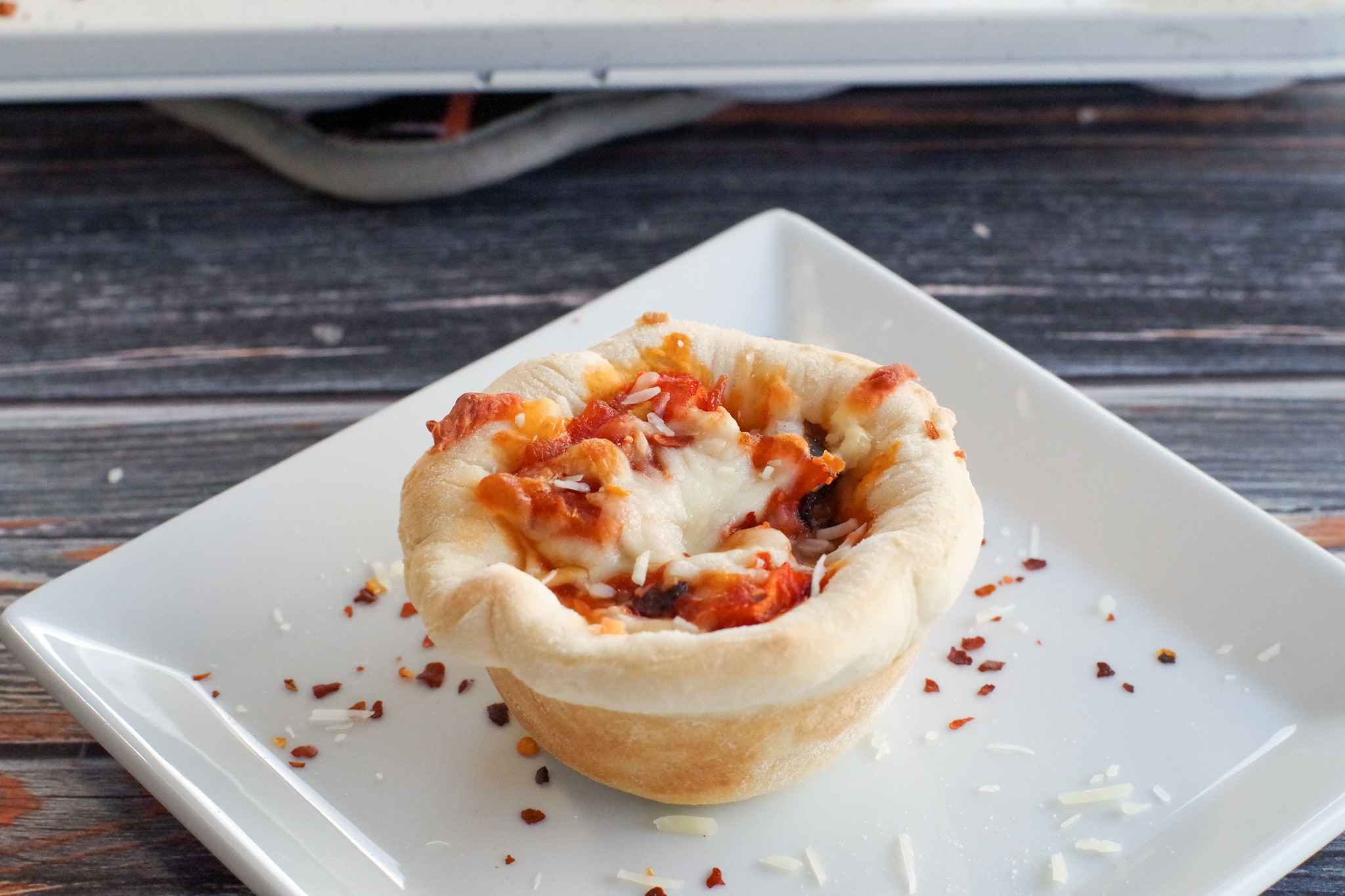 Pizza cupcake on a white plate with crushed red pepper and parmesan cheese sprinkles on plate