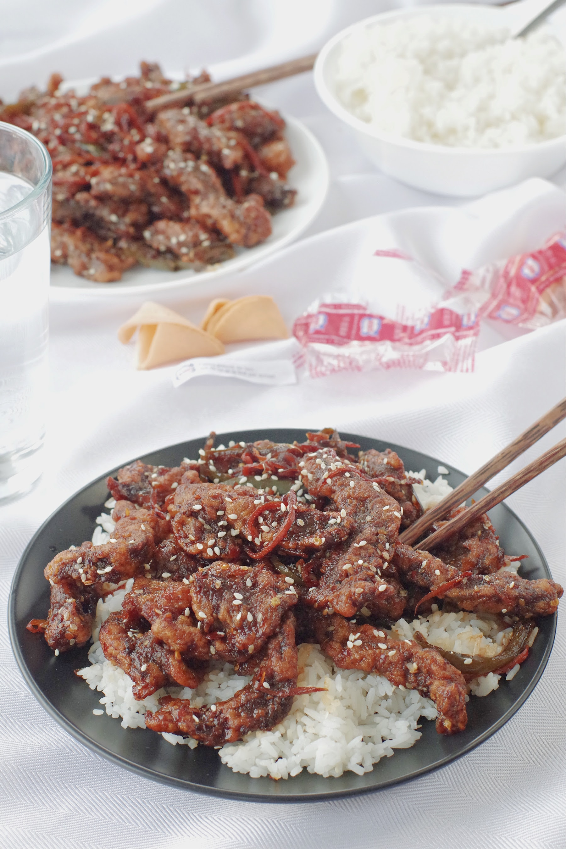 ginger beef over rice on black plate, with chopsticks on a white tablecloth, with a dish of ginger beef and rice in the background, as well as fortune cookies