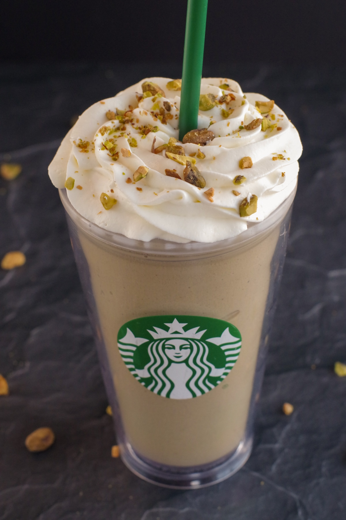Pistachio Frappuccino in Starbucks cup on black surface with pistachios around
