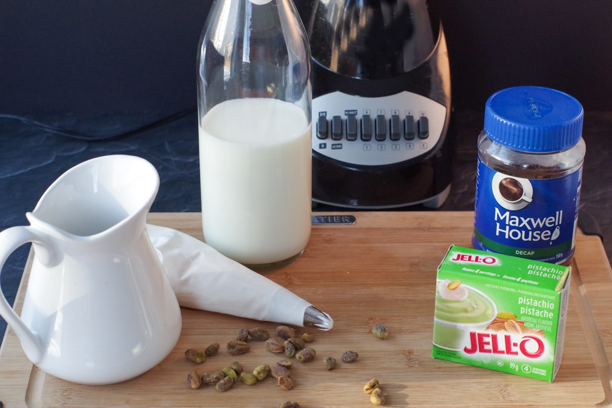 ingredients for pistachio frappuccino on cutting board with blender in background