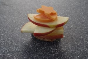 cheese shapes added to apple slices on a grey cutting board
