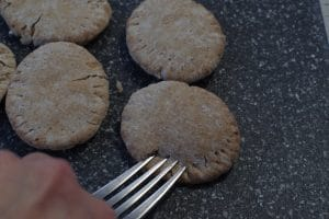 fork pressing into pita bread to make pie like imprint