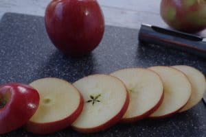 apples, sliced about ¼ inch thick, on a grey cutting board with a whole apple in the background