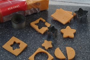 cheese cut outs with mini cookie cutters on a grey cutting board