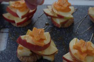 apple pie bites being garnished with additional cinnamon sugar