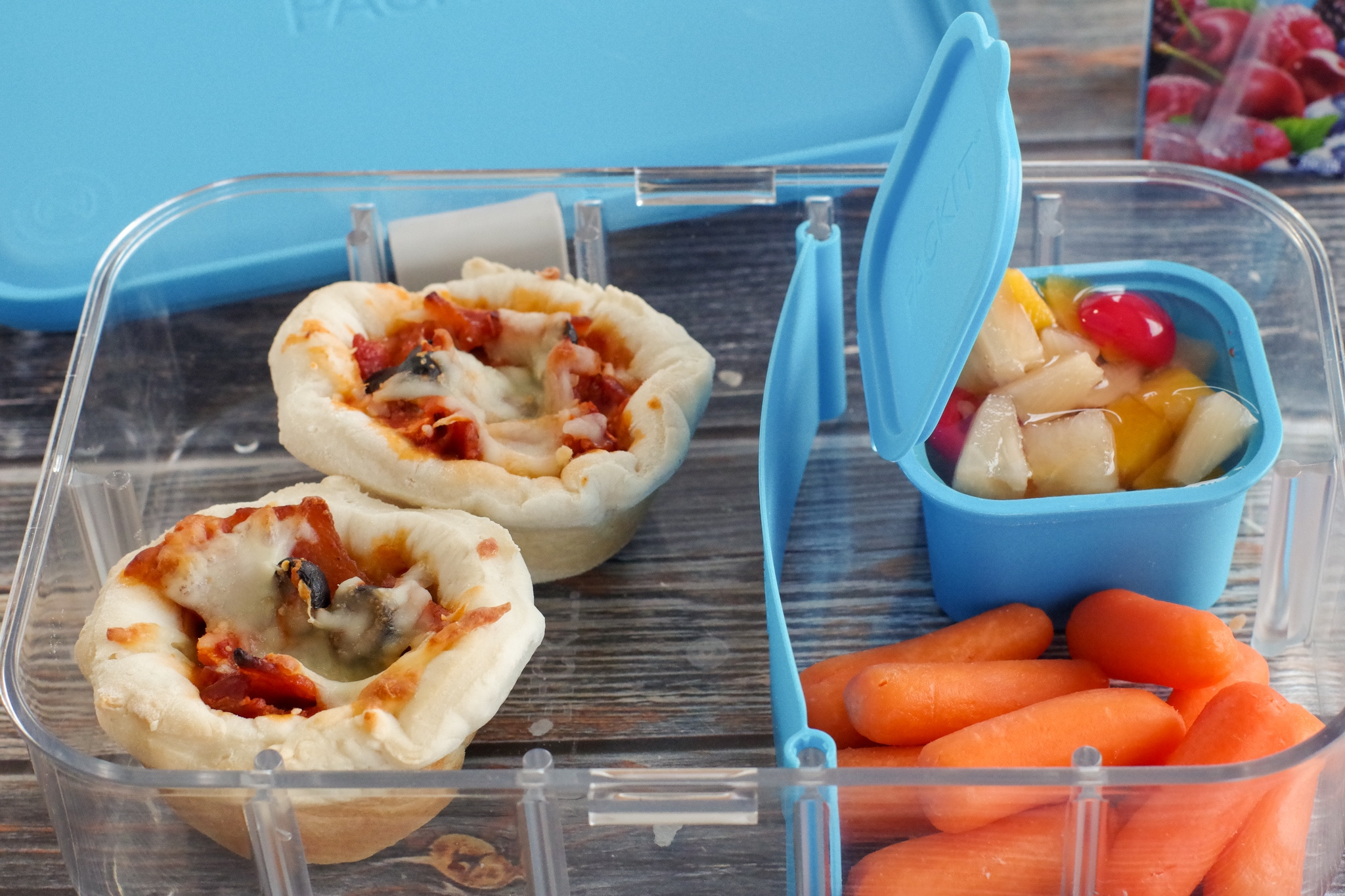 2 pizza cupcakes in a clear bento box with blue dividers, with baby carrots in one section and fruit cup in a small container in another