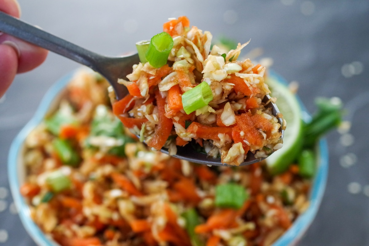 close up of asian coleslaw salad being held up on a spoon