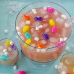 Easter punch in a trifle bowl with glasses around, as well as marshmallow Easter eggs and mini marshmallows