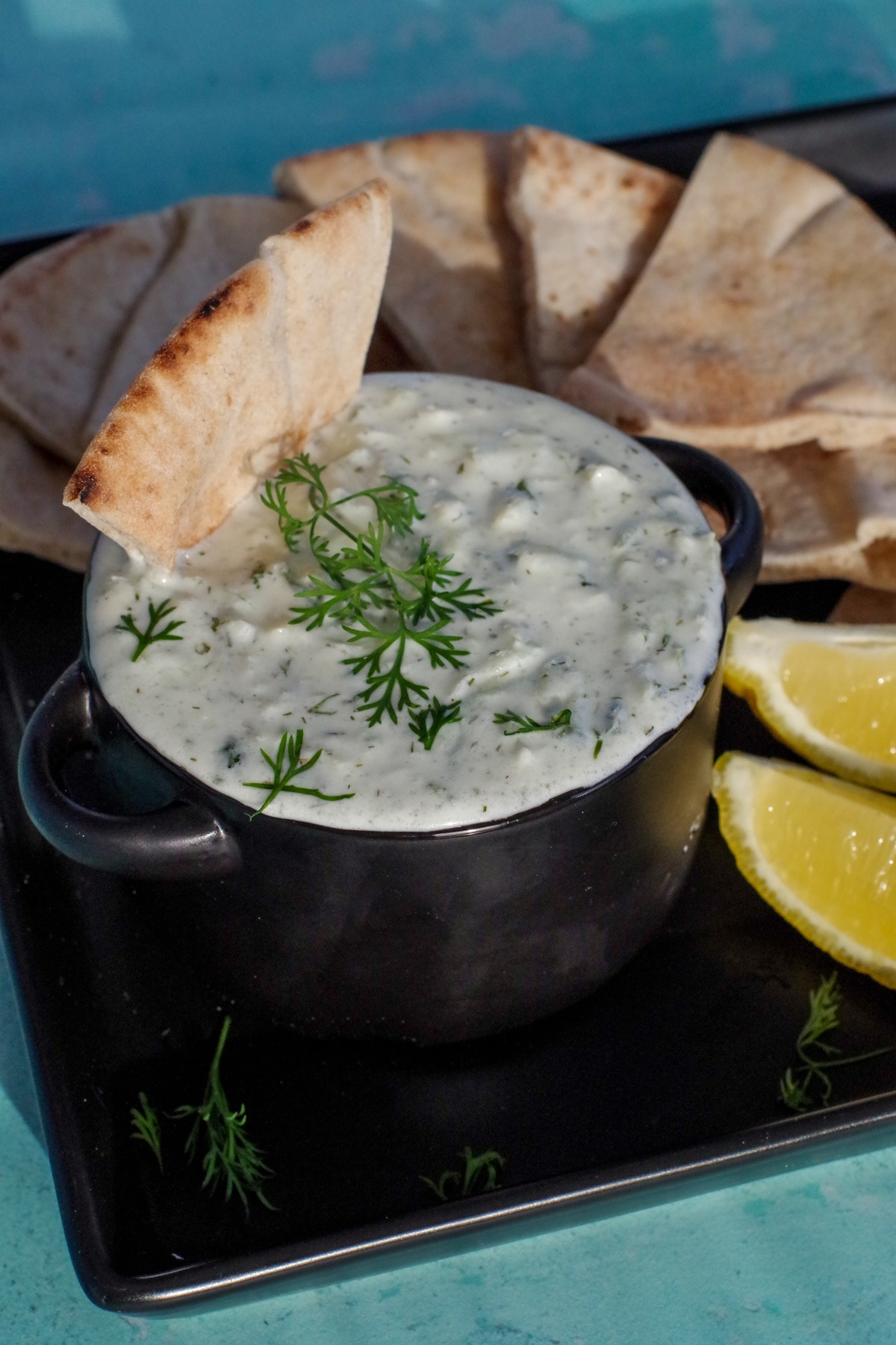 triangle of pita bread being dipped into tzatziki sauce in black bowl on black tray with pita bread in background and lemon wedges
