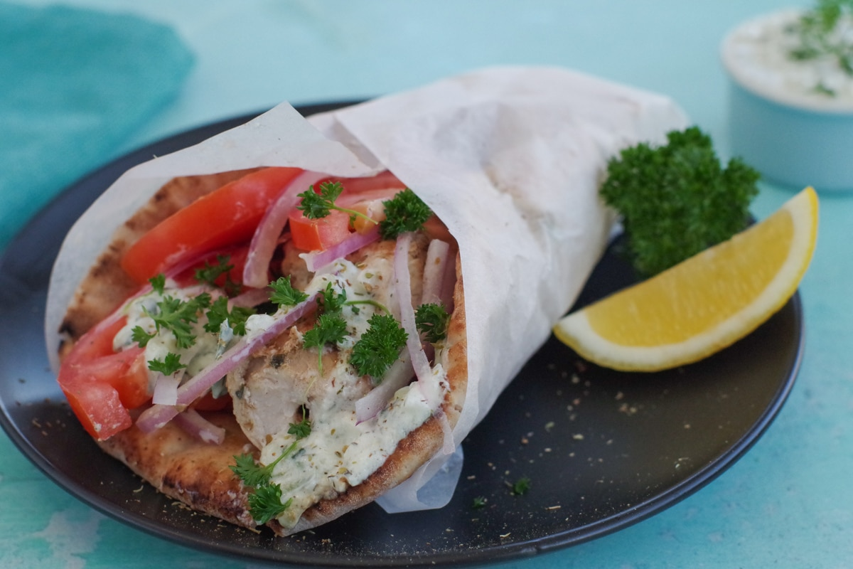 Greek Souvlaki in pita bread on black plate with lemon wedges and parsley on side and dish of tzatziki in background