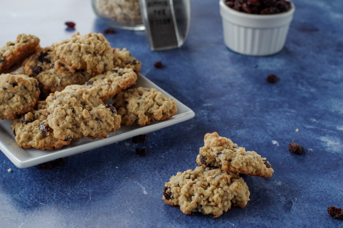 2 oatmeal raisin cookies on blue surface with plate of cookies, dish of raisins, jar of oats and scoop in the background