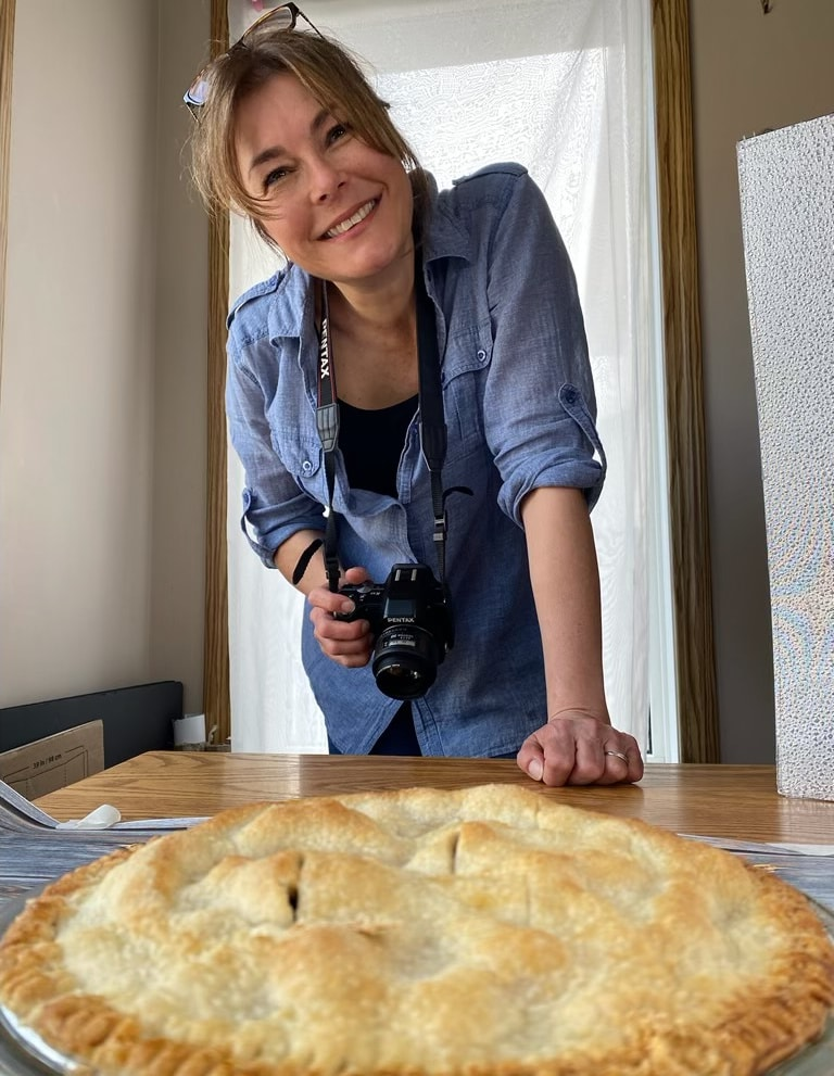 food blogger (me) photographing a pie, smiling at the camera, holding a camera