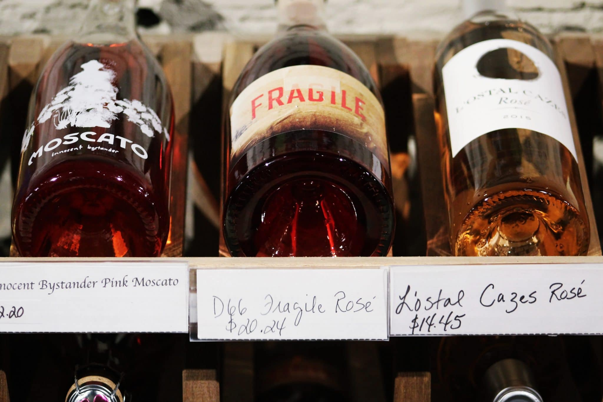 3 wine bottles, laying flat, with price tags, on a store shelf