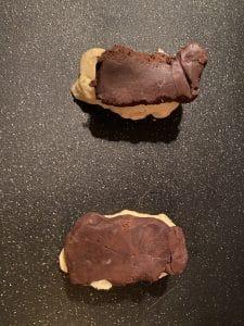 chocolate dough on top of vanilla dough on black cutting board