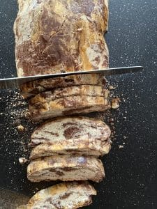 biscotti being cut with serrated knife on black cutting board