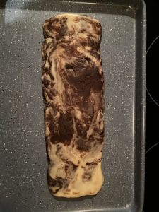 flattened biscotti log on greased baking sheet