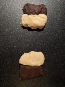 chocolate and vanilla dough, side by side, in 2 portions, on black cutting board