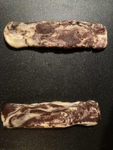 dough shaped into logs on black cutting board