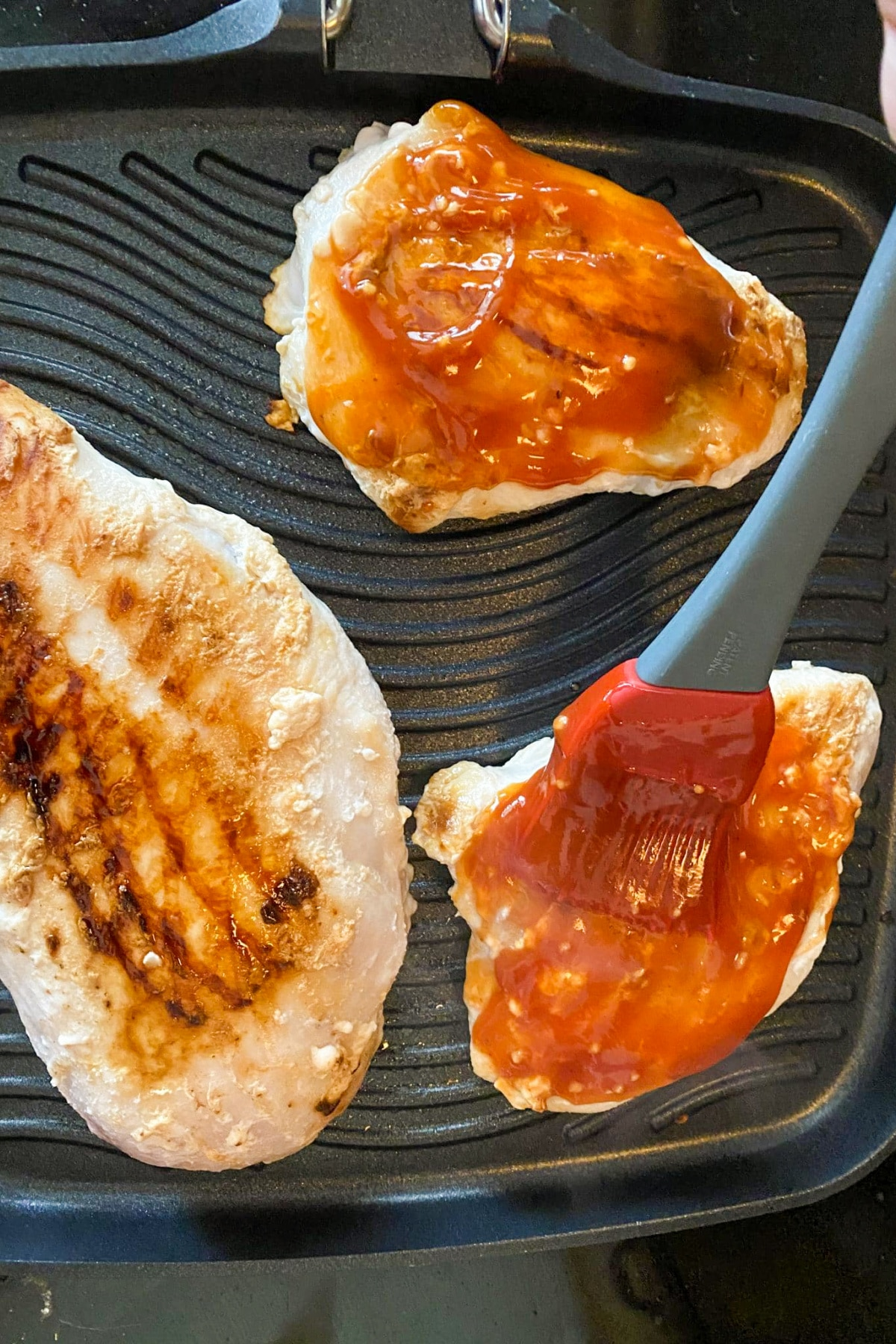 3 pieces of chicken breast on grill with BBQ sauce being spread on one piece