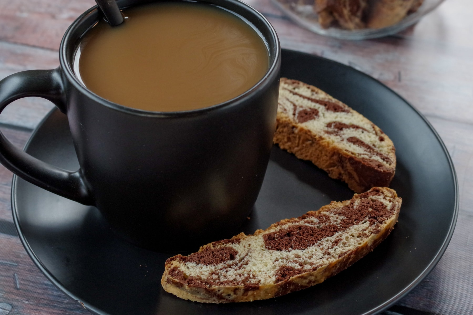 cup of coffee in a black mug on a black plate with 2 pieces of chocolate marble biscotti on the plate and a jar of biscotti in background