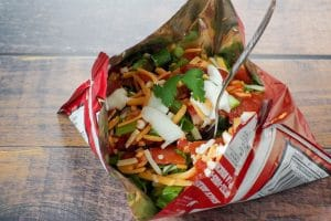 tacos in a bag with fork, on wooden surface