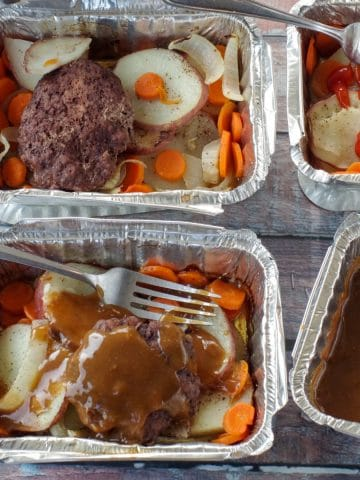 4 hamburger foil packets in aluminum foil containers with potatoes, carrots, onions and hamburgers, on wooden surface
