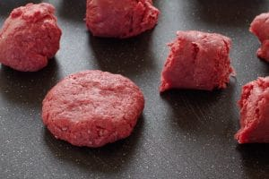 raw ground beef on black cutting board, divided into sections, with one section formed into a patty