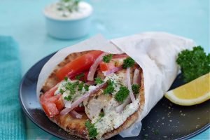 Greek chicken souvlaki wrapped in pita with tomatoes, red onion, tzatziki and parsley, wrapped in paper on black plate
