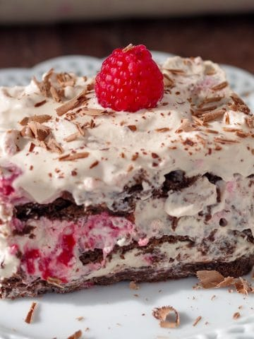 raspberry dulce de leche icebox cake on white plate with glass dish of cake in the background