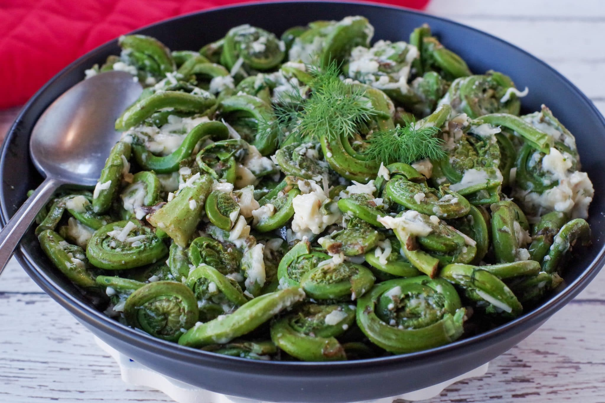Cheesy Sauteed fiddleheads in a black bowl with a red oven mitt in the background