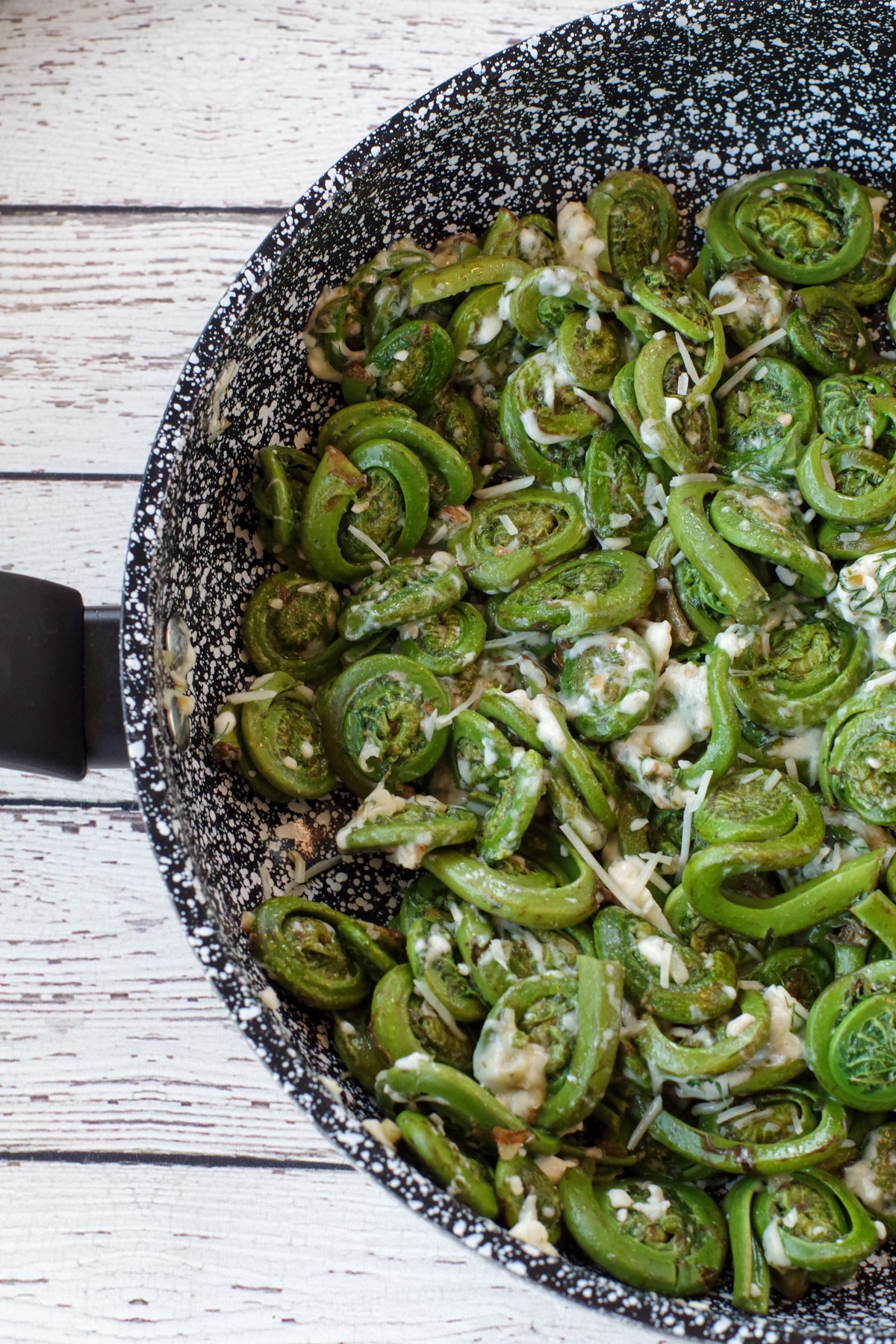 a half pan of sauteed fiddleheads on a white faux wooden surface