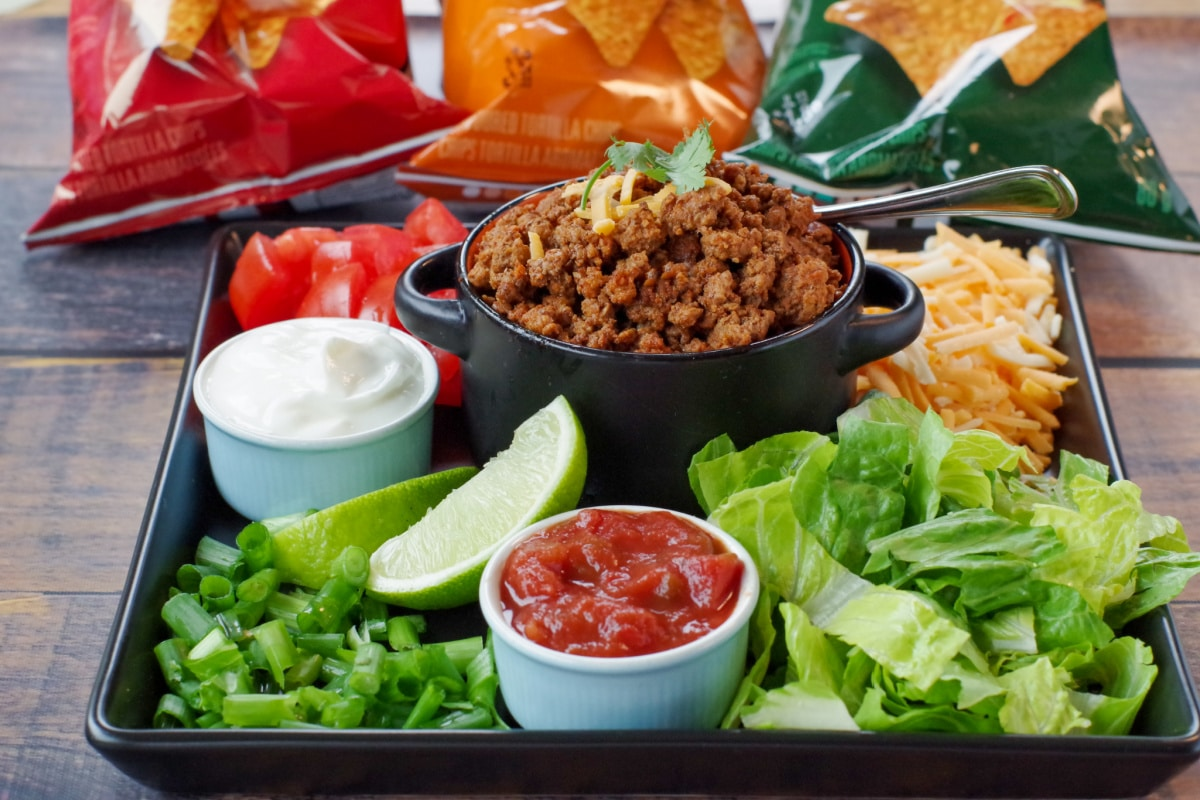 black tray with fixings (lettuce, salsa, sour cream, taco meat, lettuce, cheese, green onions and tomatoes, with bags of tortilla chips in the backgroun