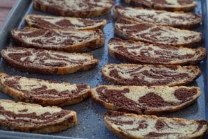 chocolate marble biscotti on a blue baking sheet