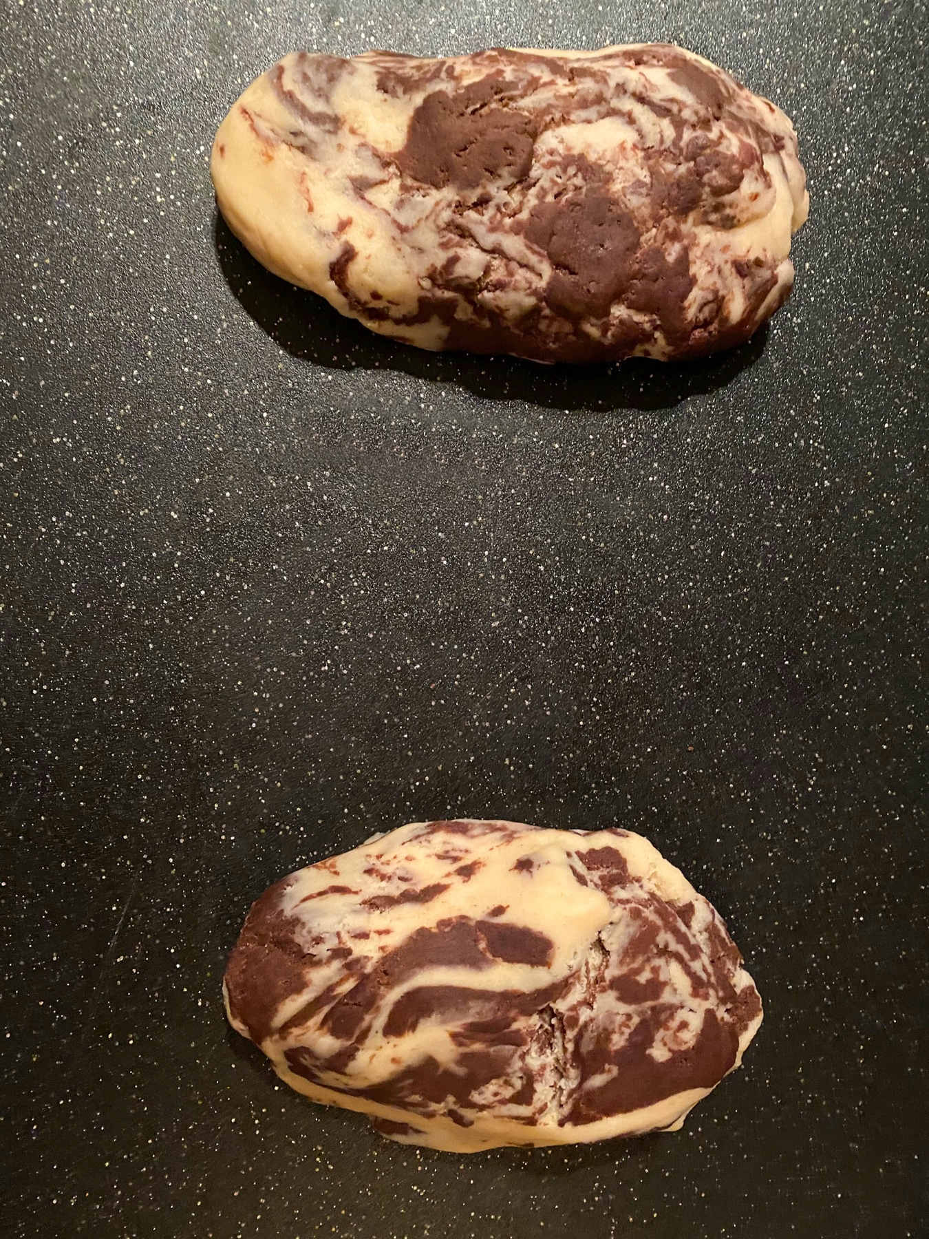 2 portions of marbled biscotti dough on black cutting board