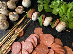 pepperoni, mushrooms, green peppers on cutting board with skewers