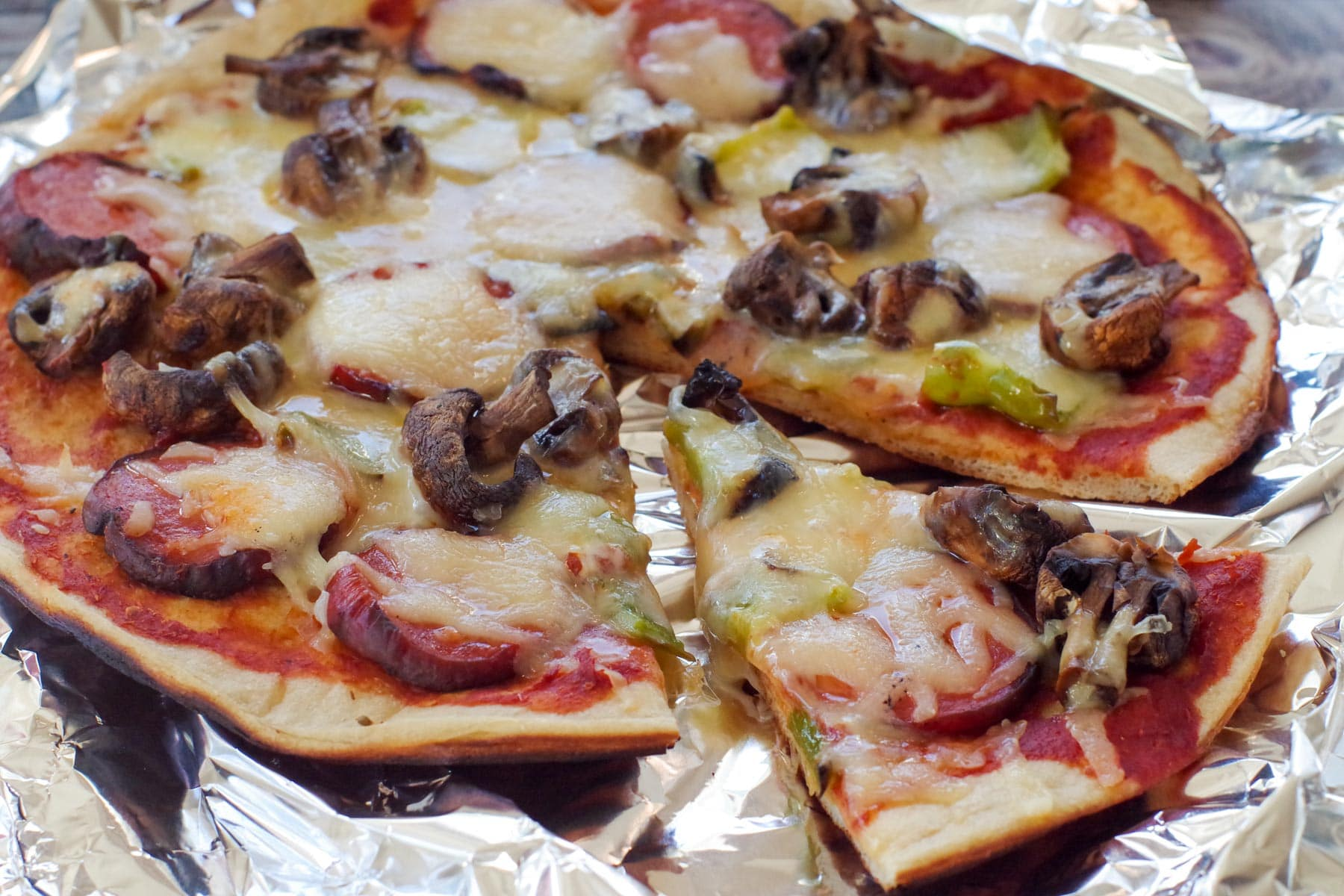 camping pizza on foil, with a slice removed